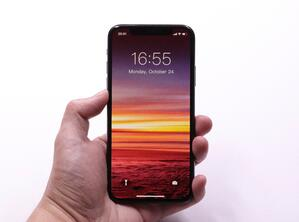 person holding iphone displaying lock screen with sunset display background